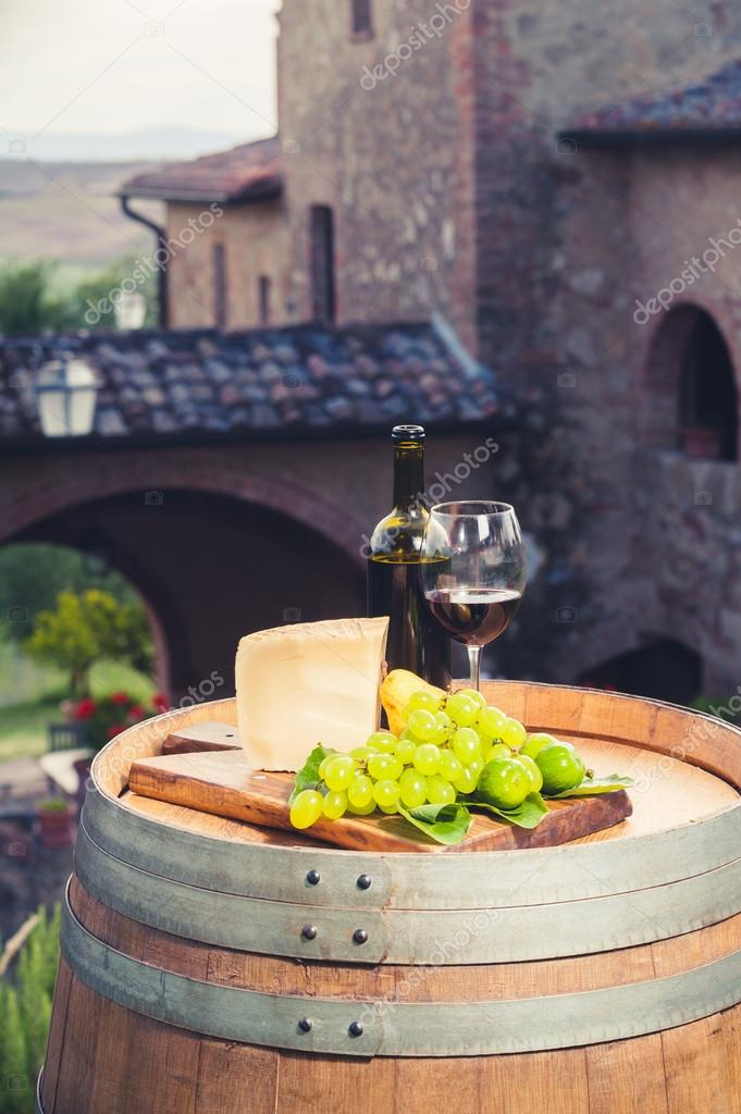Red wine, pecorino cheese, grapes, bottle and glass on wooden ba