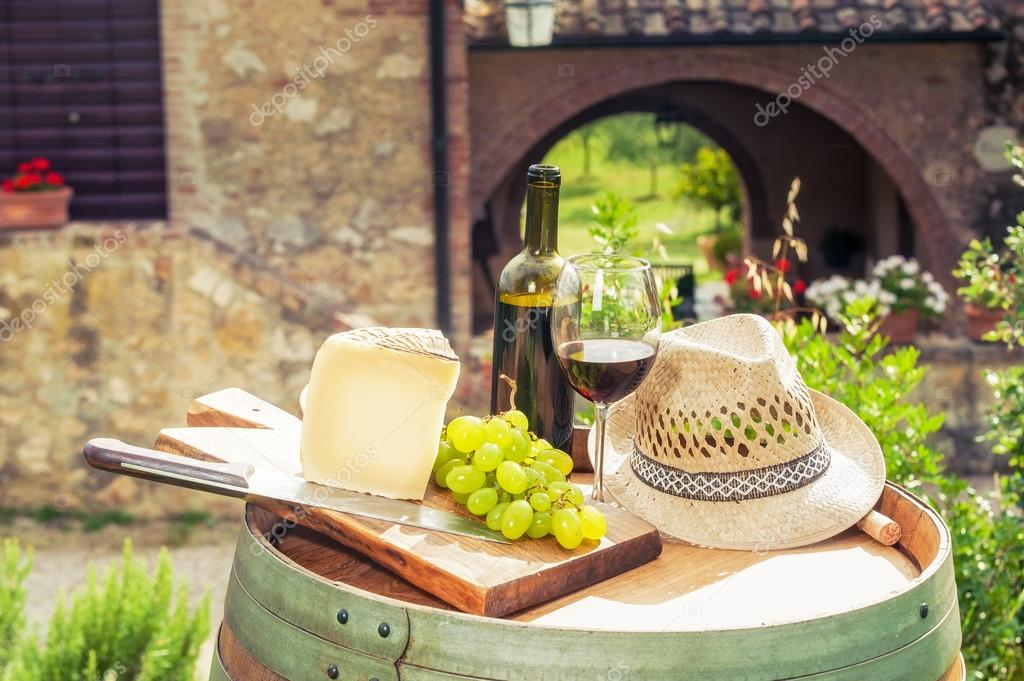 Red wine, cheese, grapes and a straw hat on a wooden barrel on t