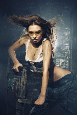 Young, sexy girl in a glasses hold a perforator.