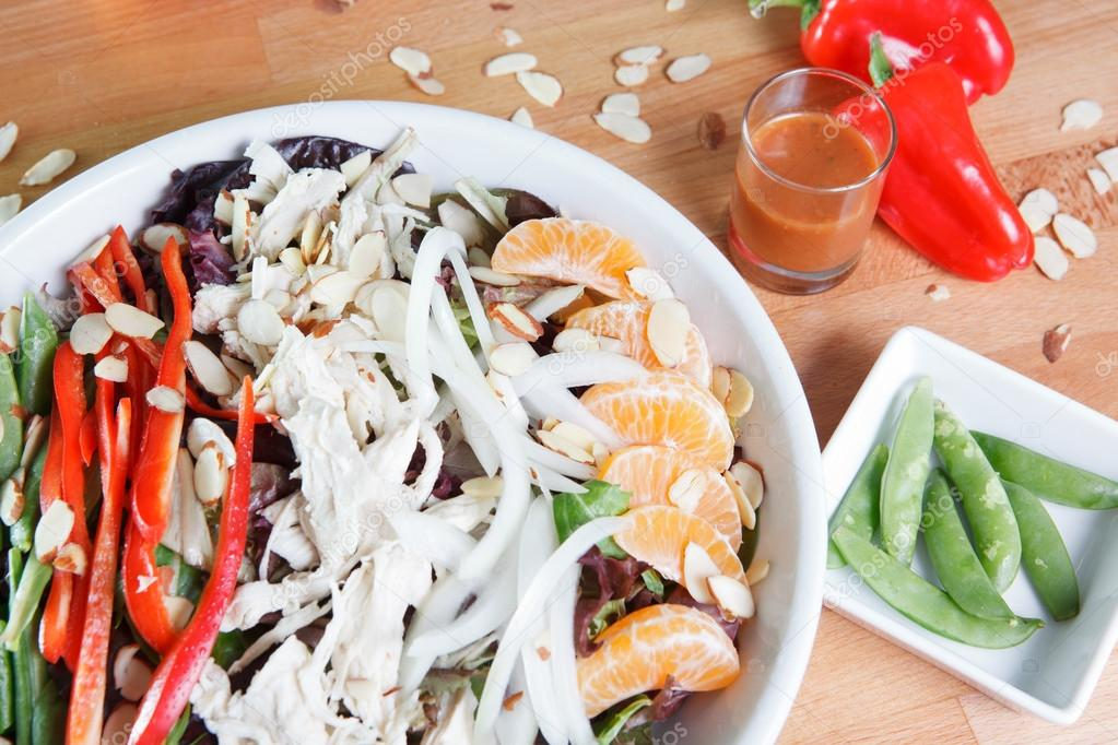Colorful large serving of Spicy Asian themed chicken and citrus salad with nuts, peppers, fruit and vegetables