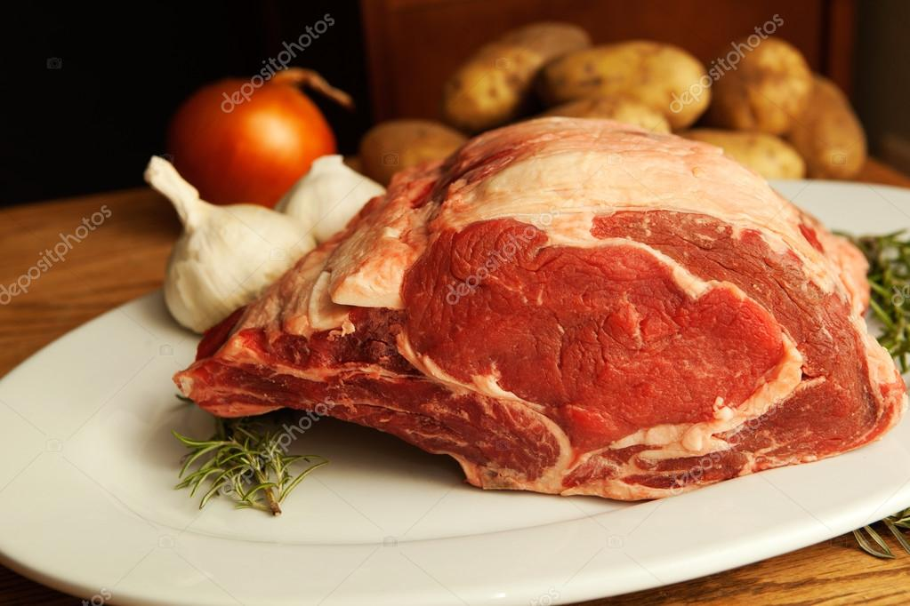 Beautifully marbled seven pound ribeye roast bone in, laying on its side on a white plate with colorful garnish ready to cook.