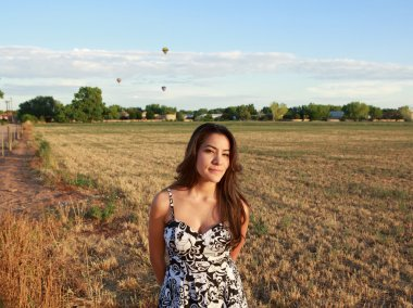 Attractive Hispanic woman standing in open field at sunrise against backdrop of hot air balloons