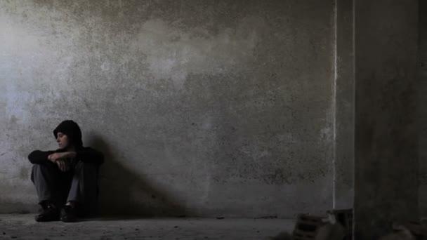 Depressziós fiatal ember elhagyott épület-a munkanélküliség depresszió