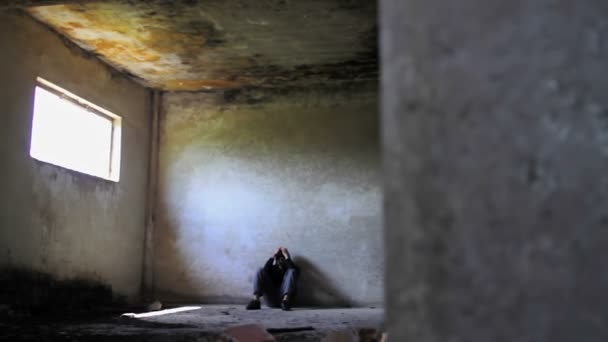 Hajléktalan depressziós fiatal férfi a munkanélküliség elhagyott épület
