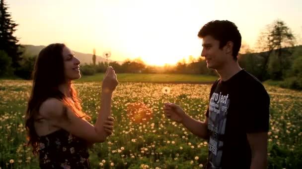 roztomilý mladý pár foukání pampelišky, směje se při západu slunce v létě