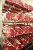 kusy hovězího masa na policích v jatkách