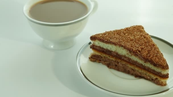šálek kávy s mlékem a kus čokoládového dortu