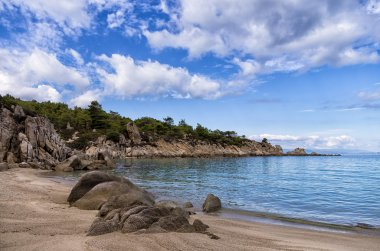 Sandy beach in Sithonia, Chalkidiki, Greece, under a cloudy sky