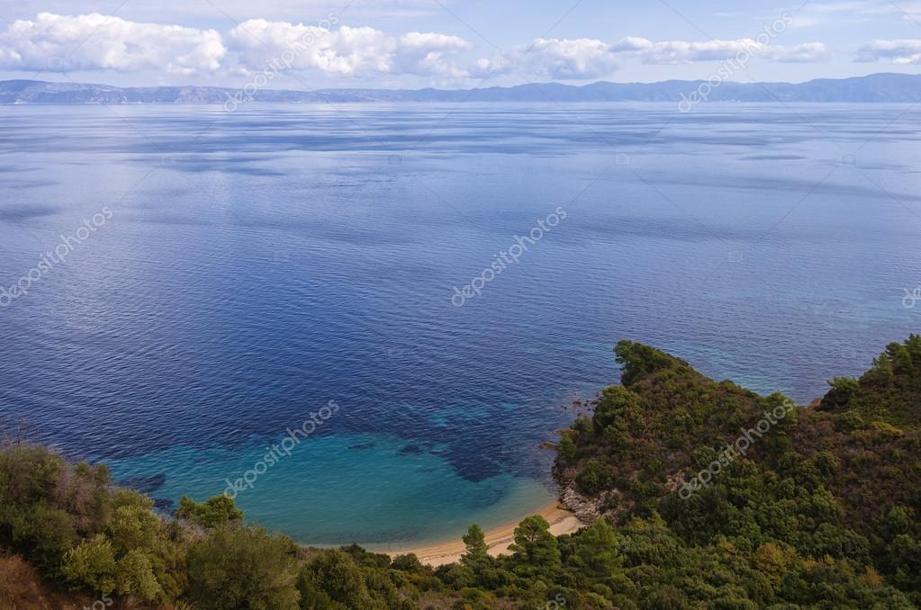 View to the sea from the top of the mountain, with a hidden little sandy beach, in Sithonia, Chalkidiki, Greece