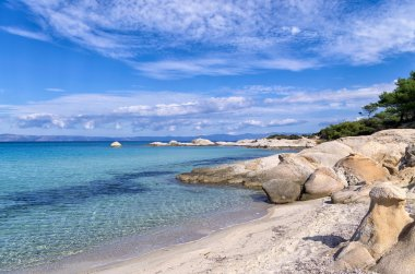 Rocks in a sandy beach in Sithonia, Chalkidiki, Greece, with crystal clear water