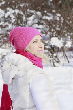 girl in pink hat looking at the winter sun