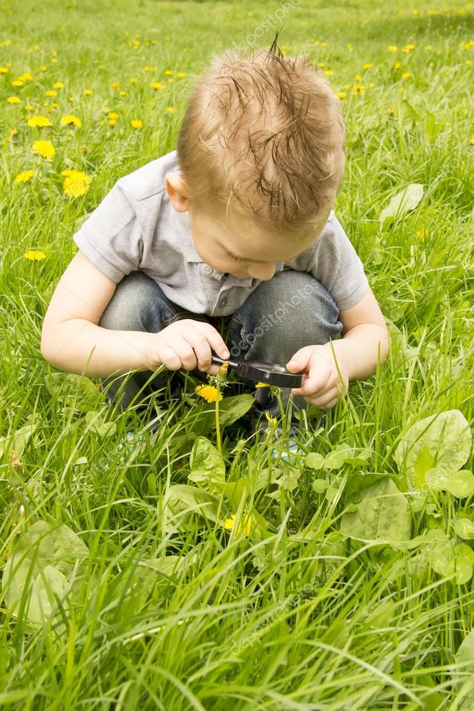 boy looking through a magnifying glass on the grass