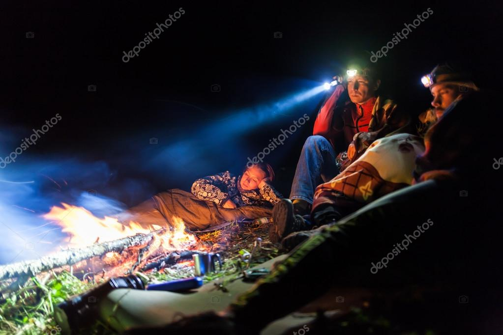 Bonfire in a camp in the mountains and the light of flashlights