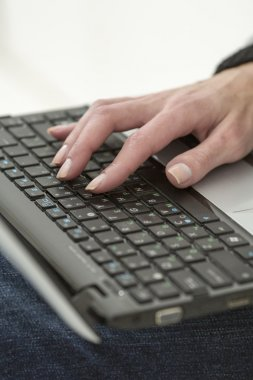 Woman with beautiful nails prints on the laptop