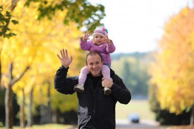 Happy father with the child walks in park
