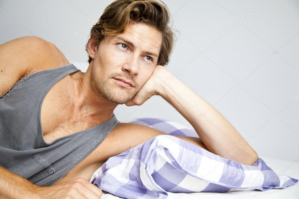 Young Man Lying In Bed Daydreaming Stock Photo