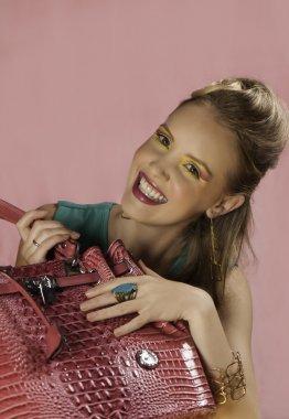 Laughing blonde retro woman with pink handbag