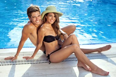 Happy beautiful young couple at the swimming pool