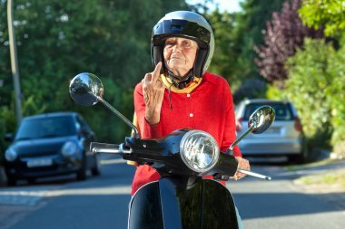 Angry old lady on a scooter making a rude gesture