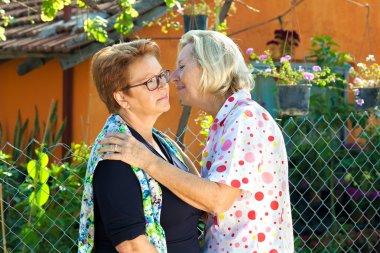 Elderly ladies greeting each other.