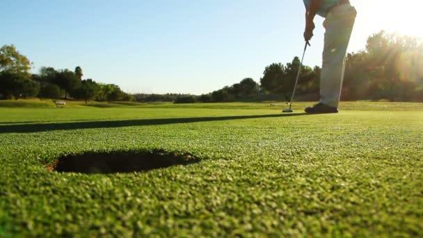 Mann golft und setzt Ball in Loch