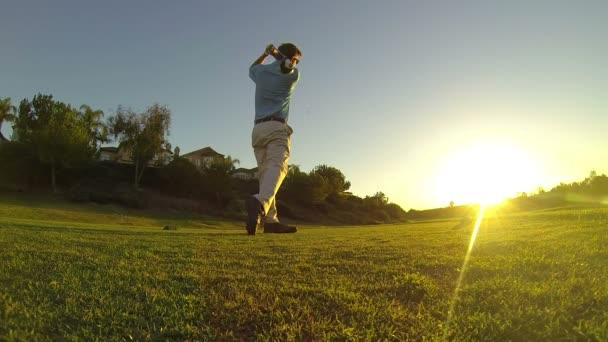 mladý muž hrát golf na golfovém hřišti