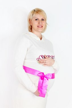 Happy pregnant woman in white with pink ribbon on belly on white