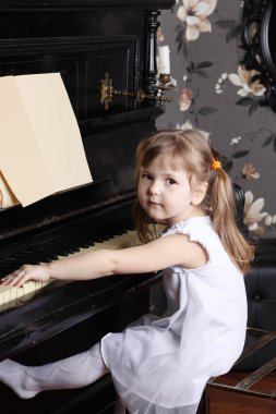 Little beautiful girl in white dress sits at black piano with mu