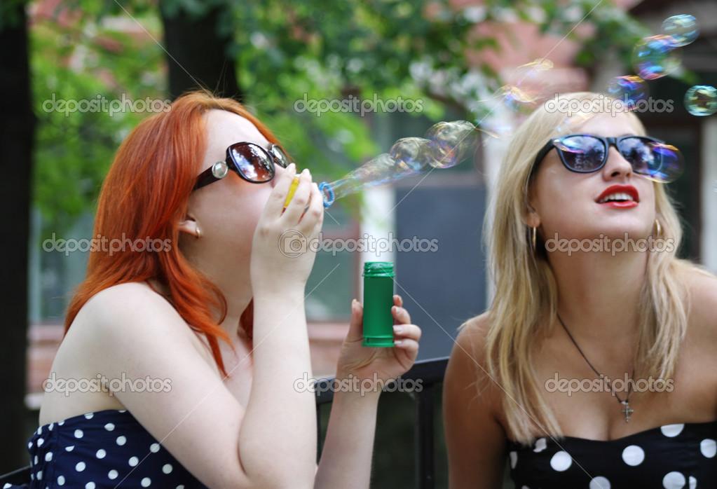 61019a910e87 Dos chicas guapas en burbujas de gafas de sol en parque en verano ...