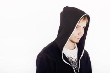Serious handsome young man in black hoodies looks away in studio