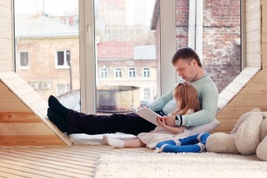 Pretty little blonde girl and father sit near window and read bo