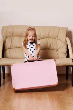 Pretty little blonde girl drags big pink suitcase near sofa in r