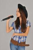 Nachdenklich hält das Mädchen mit schwarzem Hut, kariertem Hemd mit kurzen Ärmeln und Jeans ein schwarzes Mikrofon in der Hand