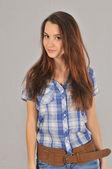 ein junges Mädchen in einem Hemd mit kurzen Ärmeln und Jeans mit einem Lächeln blickt voraus