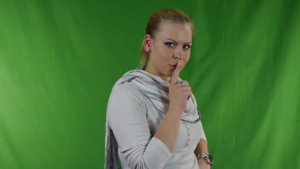 mladá žena uvedení prst na rty pro Ššš gesto - tajemství Psst