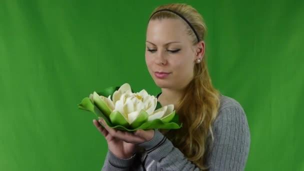 s úsměvem mladá dívka drží bílý leknín na tvář, izolované na zelené obrazovce. č.01
