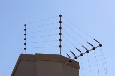 Electric Fence Against Blue Sky Atop Boundary Wall