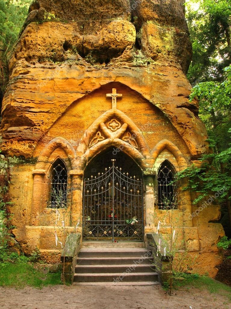Small village chapel hewed into sandstone block. Small statue of Madonna in hewed cave, flower at Madonnas legs.