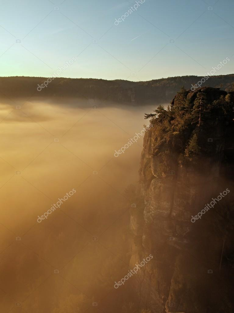 Sunrise in a beautiful mountain of Czech-Saxony Switzerland. Sandstone peaks increased from foggy background, the fog is orange due to sun rays.