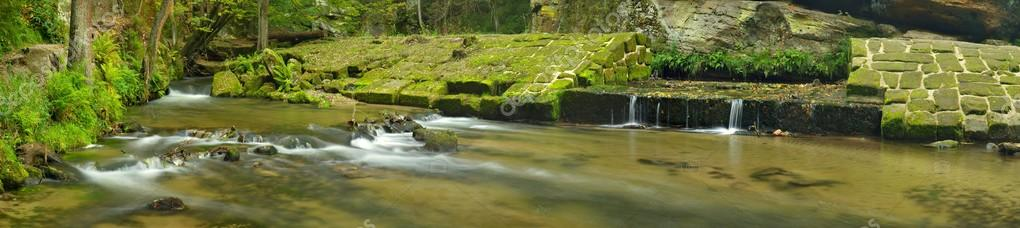 Ruins of sandstone weir on small mountain river. Stream is flowing over sandstone blocks and makes milky water.