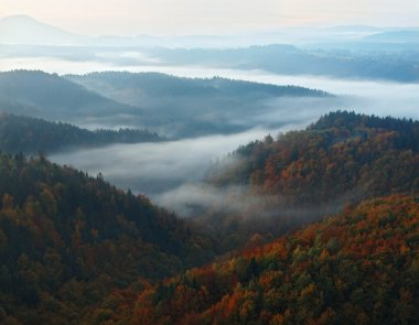 Unrise in a beautiful mountain of Bohemian-Saxony Switzerland. Sandstone peaks and hills increased from foggy background, the fog is orange due to sun rays.