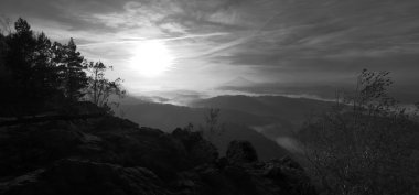 Sunrise in a beautiful mountain of Bohemian-Saxony Switzerland. Sandstone peaks and hills increased from foggy background. First sun rays. Black and White photo.