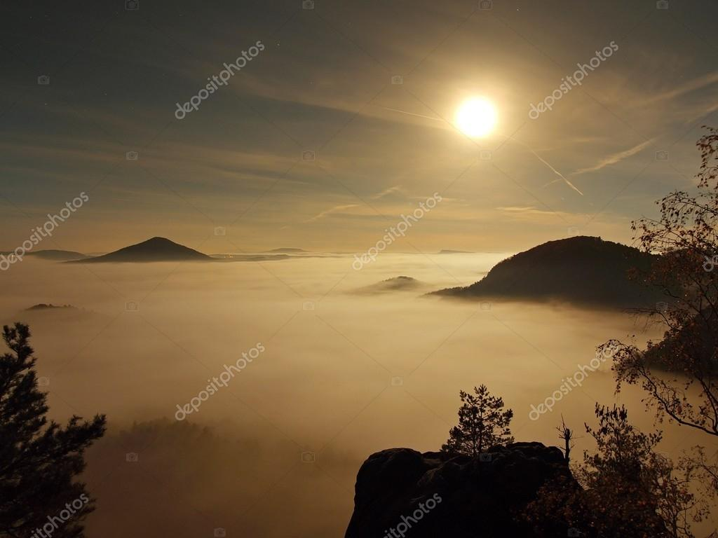 Full moon night with sunrise in a beautiful mountain of Bohemian-Saxony Switzerland. Sandstone peaks and hills increased from foggy background, the fog is orange due to sun rays.
