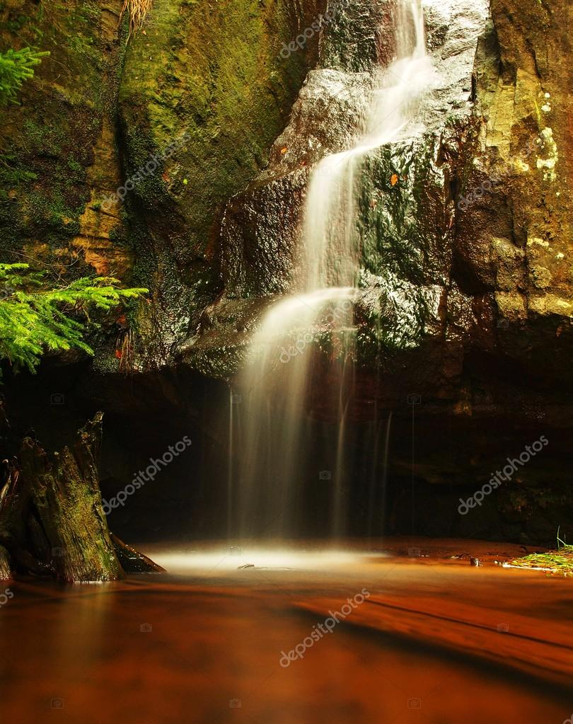 Cascade or small waterfall on fresh mountain stream, water is running over mossy sandstone block and jump down into small creek below. Water streams with sun rays, orange sand with sediments below.