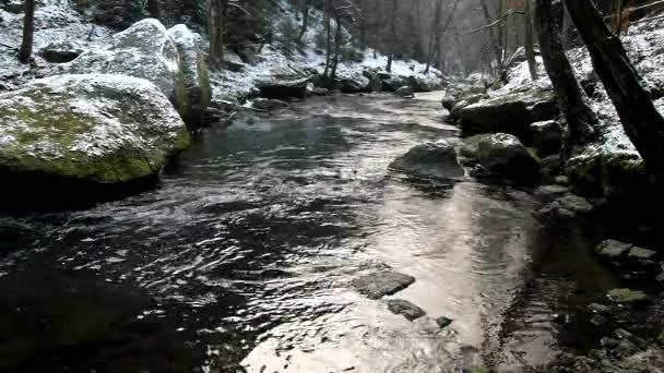 velké balvany v čisté vodě proudu. zima začíná v horské řeky.