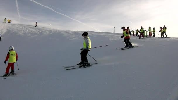 vrchol hory s svah pro sjezdové lyžování v Alpách lyžařské středisko, banda lyžařů z lyžařské školy těší čerstvý prachový sníh na svahu. slunný zimní den v Alpách