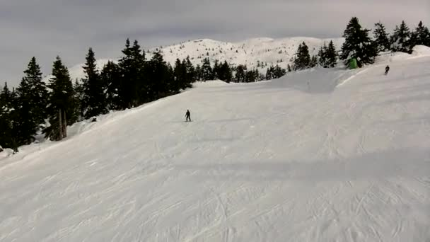 pohled z lanovky na sjezdové lyžování a snowboardu na zasněžené sjezdovky v areálu Alpy.