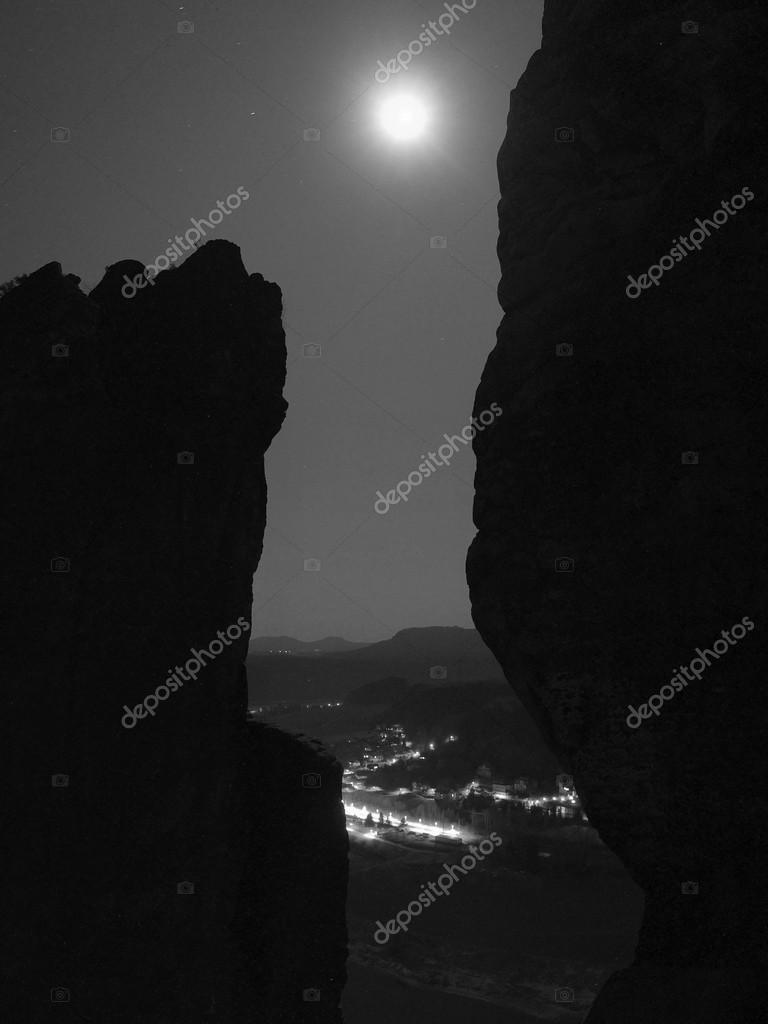 Full moon above rocks, fog is shaking above river and town on river banks.  Black and white photo.