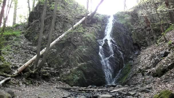 Kaskade auf kleinem Gebirgsbach, Wasser läuft durch große Risse im Basaltgestein und Blasen bilden sich auf ebenem milchigen Wasser.