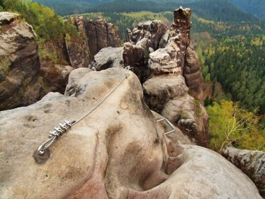 Easy via ferrata in sandstone rock of Saxony Switzerland. Iron twisted rope fixed in block by screws snap hooks.